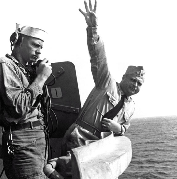 370 CDR Miller giving signal to up anchor.